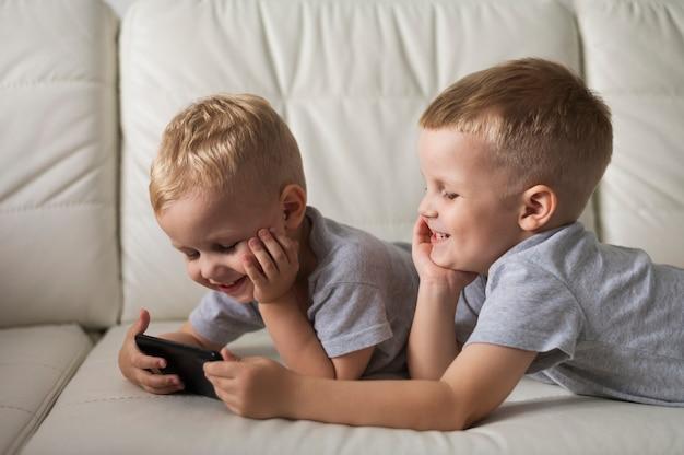 Вид сбоку братья играют на смартфоне