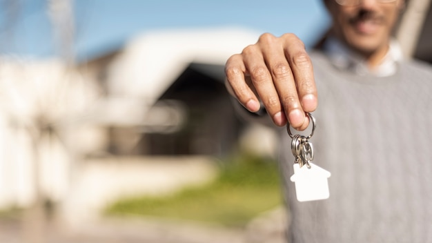 家の鍵の正面を保持しているぼやけている人