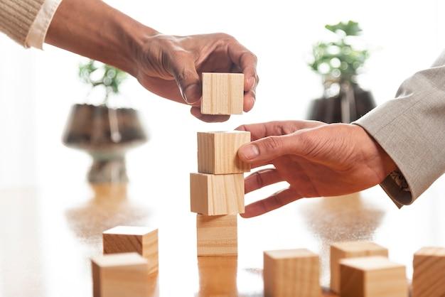木製キューブの山を構築する人々