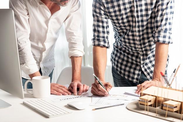 家の設計図について交渉する人々