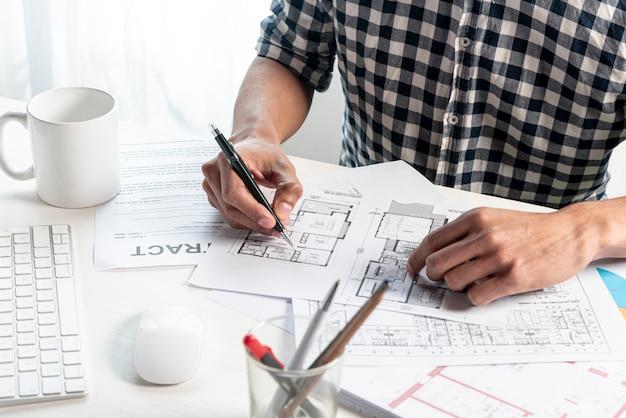 Высокий вид человека, создающего план дома