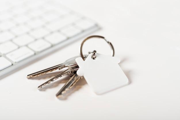 白い背景の上のキーボードと家の鍵
