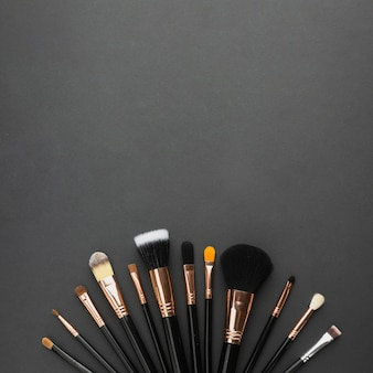 Рамка сверху с кистями для макияжа и черным фоном
