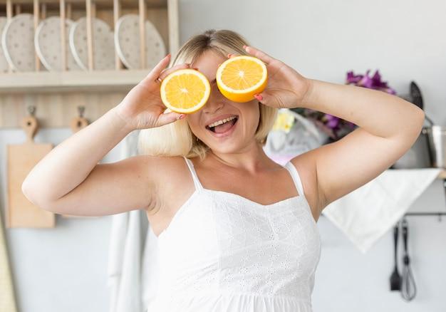 半分にされたオレンジで彼女の目を覆っているスマイリー妊娠中の女性