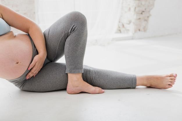 Беременная женщина делает упражнения в помещении