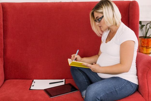 Беременная женщина пишет на ноутбуке