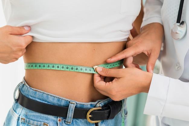 Врач крупным планом измеряет живот женщины