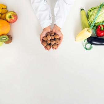 Крупным планом лицо с овощами, держа орехи