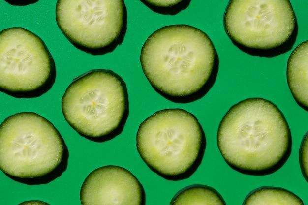 Нарезанный огуречный узор на зеленом фоне