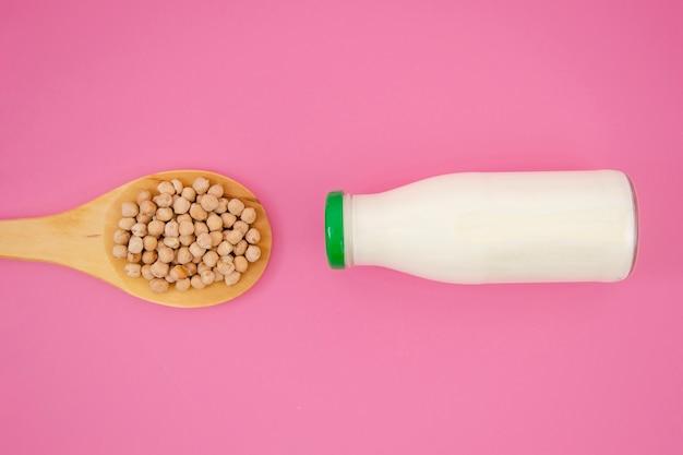 ピンクの背景にミルクとトップビューナッツスプーン