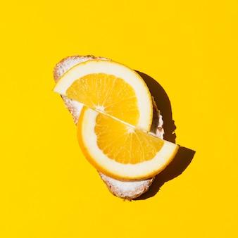 Вид сверху свежий апельсиновый бутерброд на желтом фоне