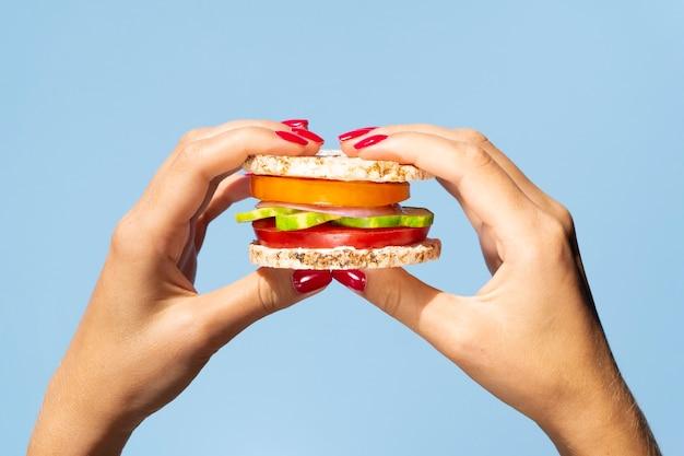 健康的な野菜のサンドイッチを持っている人
