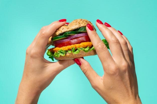 新鮮なおいしいハンバーガーを持っている人