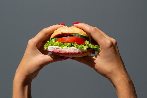 Женщина, держащая вкусный вегетарианский бургер