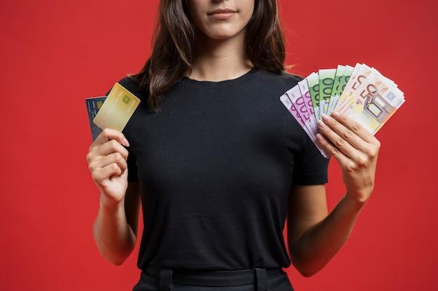 彼女のショッピングのお金を示す正面の女性