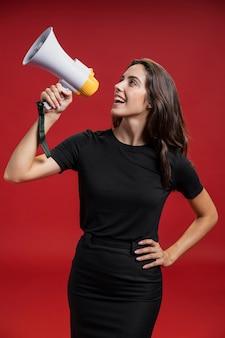 Красивая женщина кричит через мегафон