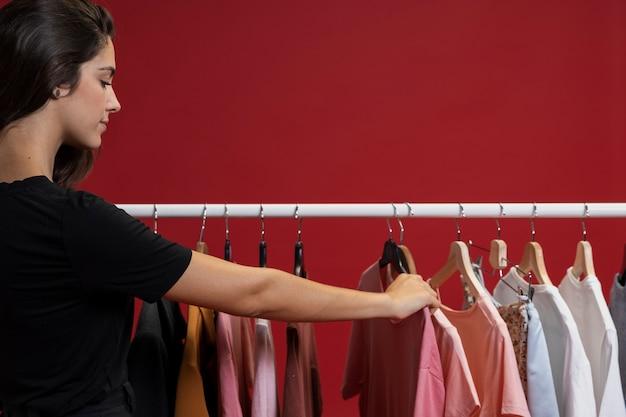 Женщина смотрит через футболки