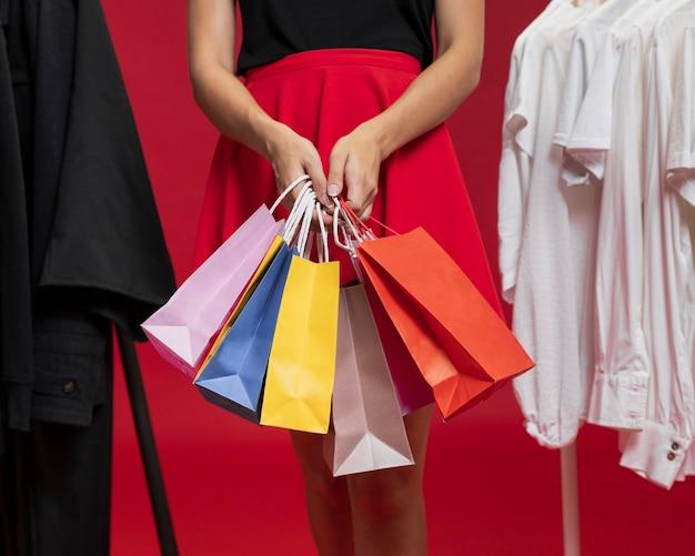 Женщина в красной юбке держит сумки