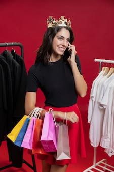 Женщина вид спереди на покупки разговаривает по телефону