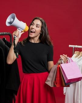 Улыбающаяся женщина с покупками кричит в мегафон