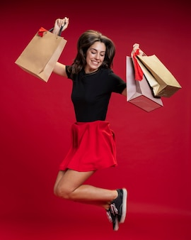 Женщина прыгает, держа ее сумки