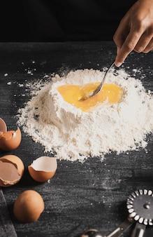 小麦粉と卵黄をスプーンで混ぜてクローズアップ