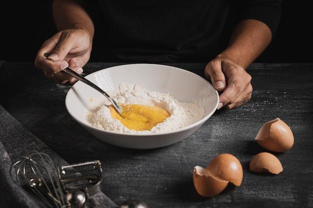 Руки пекаря крупным планом смешивают состав теста