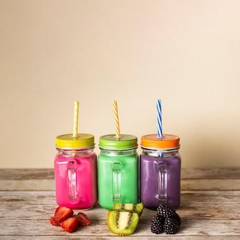 Вид спереди разноцветных смузи в баночках с фруктами