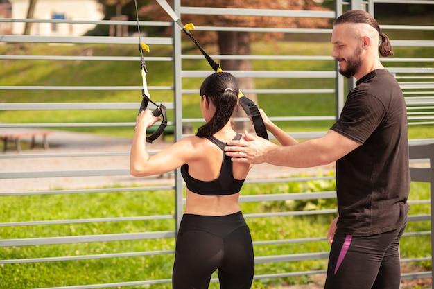 女性が正しく運動することを教える男性の友人