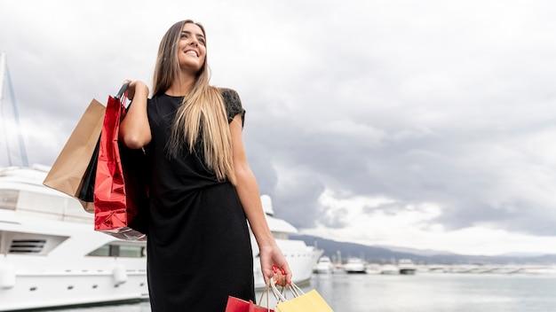 Молодая леди, показывая ее покупки счастья