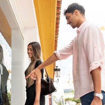 彼女の友人に何かを指している若い男