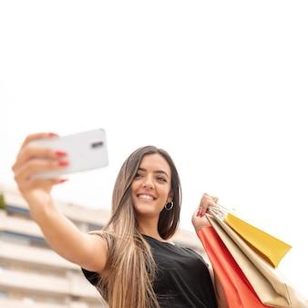 Счастливая девушка принимая селфи с бумажными пакетами