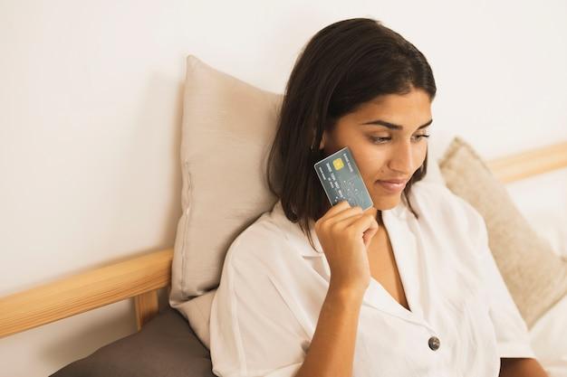 彼女の顔の横にあるカードを保持している女性