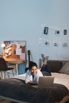 ロングショット笑顔の女性がベッドの中でラップトップに取り組んで