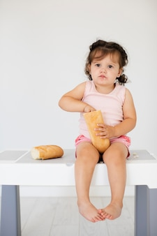 Милая девочка, играя с хлебом
