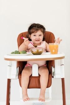 子供の椅子で食べて幸せな女の子