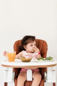 子供の椅子で食べる女の赤ちゃん