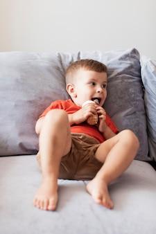 ソファーでアイスクリームを食べる陽気な少年