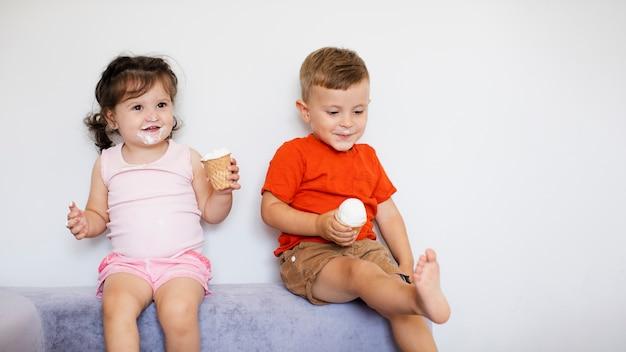 座って、アイスクリームを楽しむ愛らしい子供たち