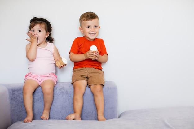 座って、アイスクリームを楽しんでいるかわいい子供たち