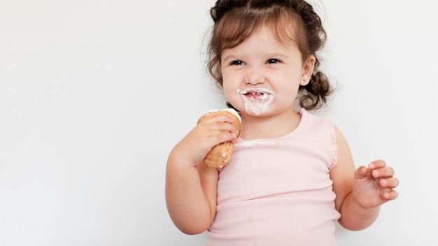 アイスクリームを食べる若い女の子をクローズアップ