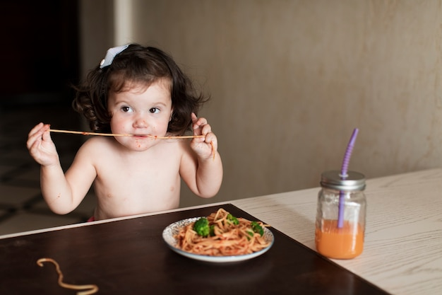 Очаровательная молодая девушка ест спагетти