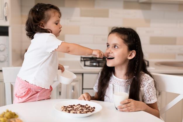 Очаровательная молодая девушка кормит свою сестру