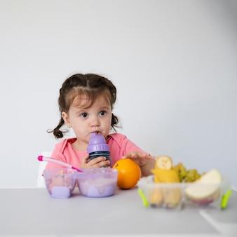 Очаровательная молодая девушка с вазой с фруктами
