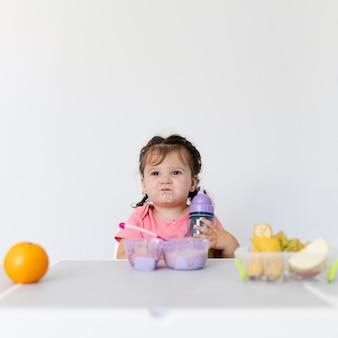 Вид спереди очаровательны молодая девушка за завтраком