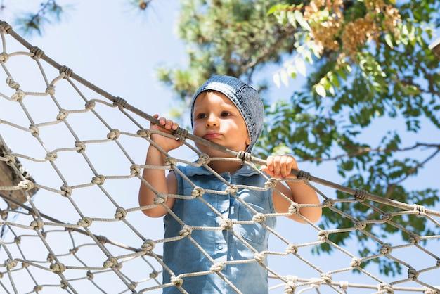 ネットを押しながらよそ見の小さな男の子
