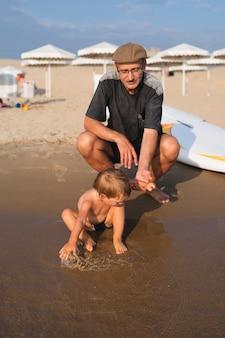 おじいちゃんの横で水で遊ぶ少年