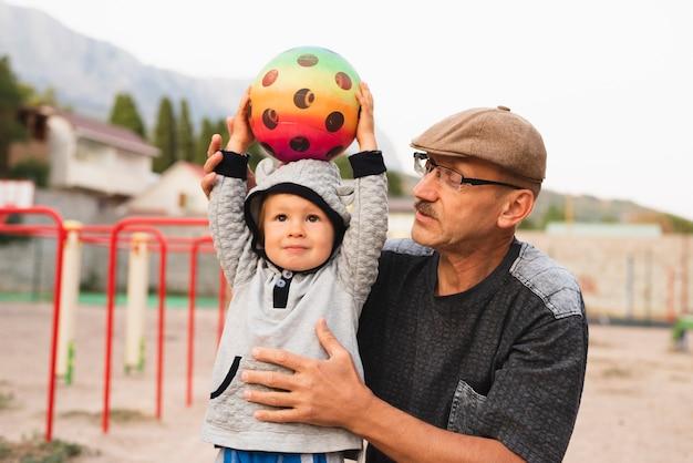 Маленький мальчик с дедушкой играет с мячом