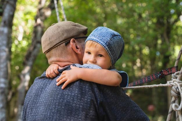 Дедушка держит в руках внука