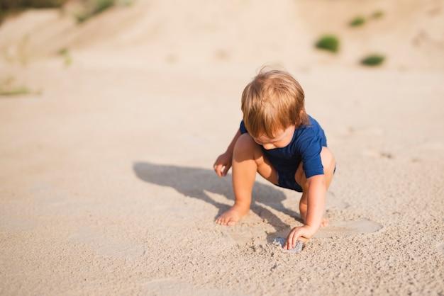 Высокий угол маленький мальчик на пляже, играя с песком
